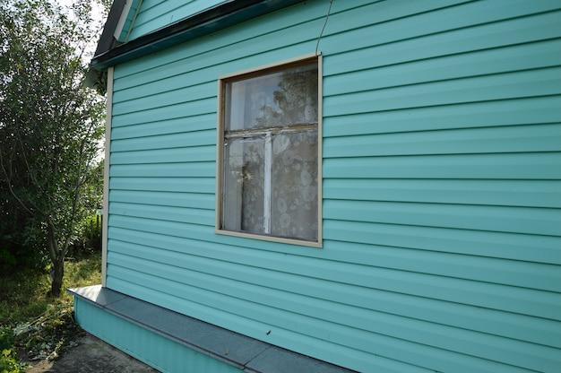 Casa de campo bonita, coberta com o tapume verde, dia de verão.