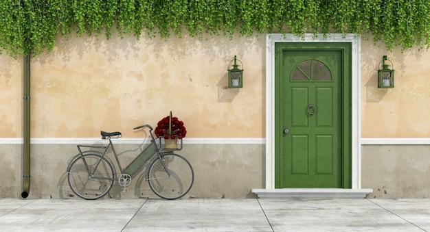 Casa de campo com porta velha e bicicleta com buquê de rosas em uma cesta de vime