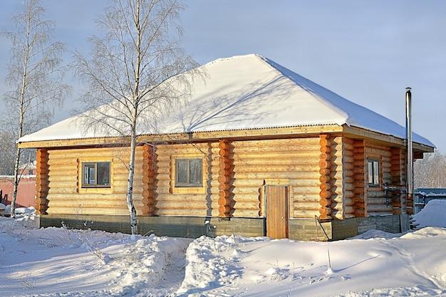 Casa de campo de madeira de madeira manchada de amarelo, inverno nevado, dia ensolarado.