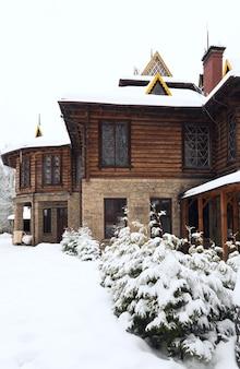 Casa de campo de madeira e pequenos abetos de inverno em frente (cárpatos, ucrânia)