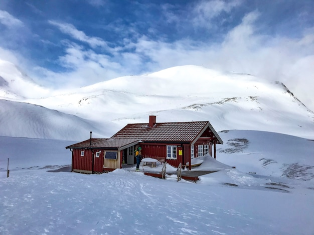 Casa de campo vermelha norueguesa no inverno, com esqui na frente, casa de noruega
