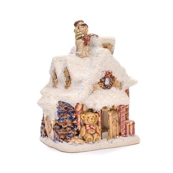 Casa de cerâmica de natal com telhado de inverno coberto de neve e um urso em um fundo branco
