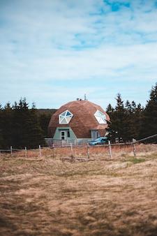 Casa de concreto branca e marrom, cercada por árvores verdes sob nuvens brancas durante o dia