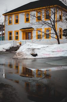 Casa de concreto marrom e branco perto do corpo de água durante o dia