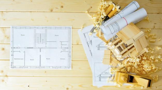 Casa de construção. obras de marceneiro. desenhos de construção, pequena casa de madeira e ferramentas de trabalho sobre fundo de madeira.