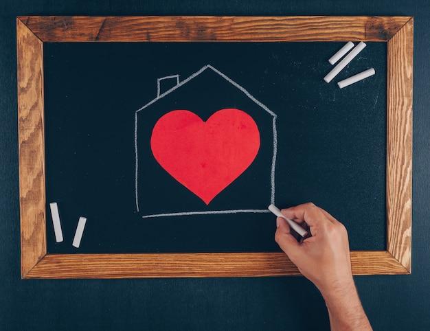 Casa de desenho homem com giz com vista superior do coração em uma moldura e preto