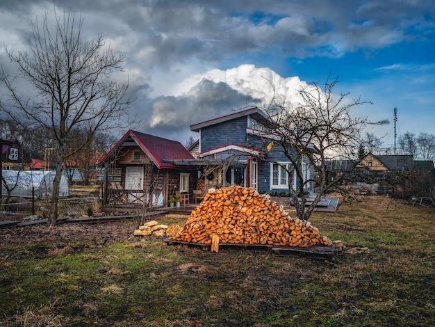 Casa de fazenda com lenha no início da primavera. vista dramática da primavera da herdade.