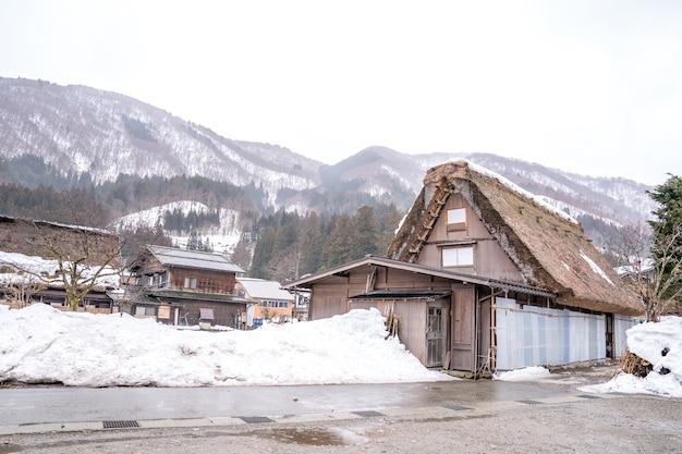 Casa de fazenda na aldeia e montanha atrás