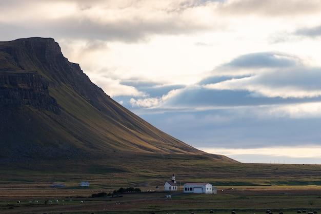Casa de fazenda nos fiordes oeste durante o dramático pôr do sol na islândia, conceito de alimentação saudável e meio ambiente