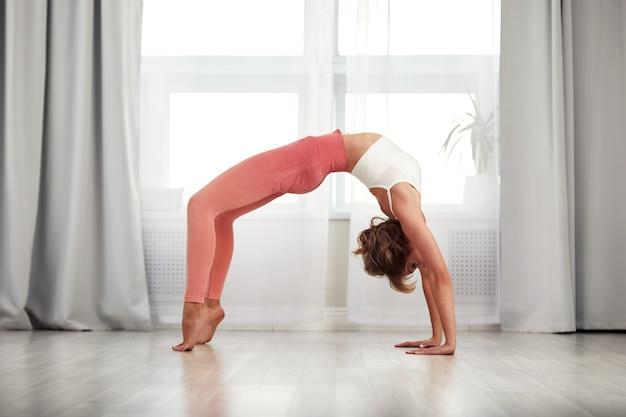 Casa de fitness. mulher bonita fazendo alguns exercícios em casa em uma sala de estar.