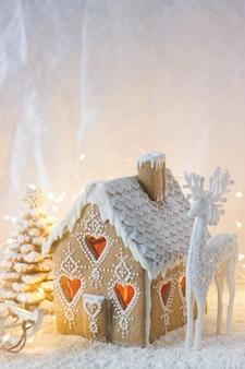 Casa de gengibre, árvores de natal e uma figura de um cervo em um fundo luminoso. efeito bokeh.