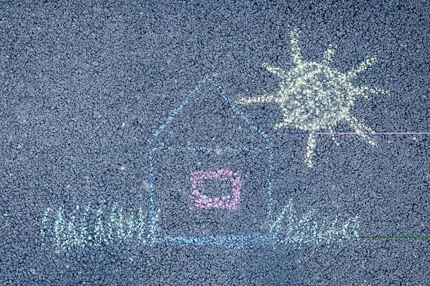 Casa de giz de cera colorido pintado, sol e grama no asfalto