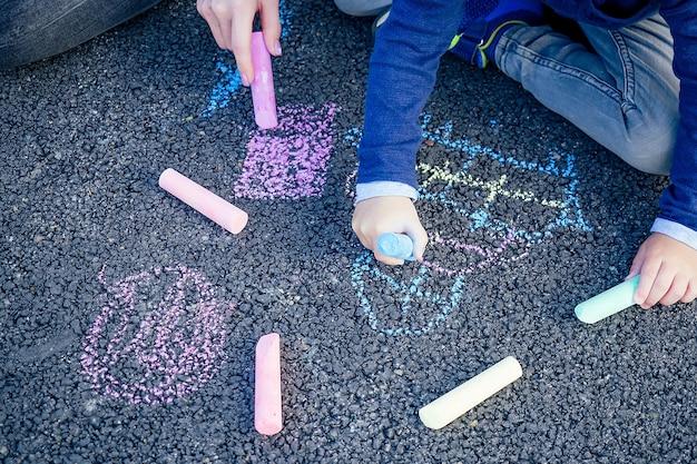 Casa de giz de cera colorido pintado, sol e grama no asfalto Foto Premium