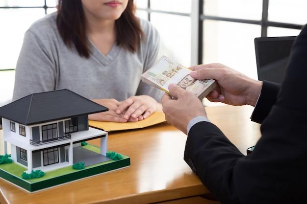 Casa de hipoteca mulher asiática com o banco e receber dinheiro baht tailandês