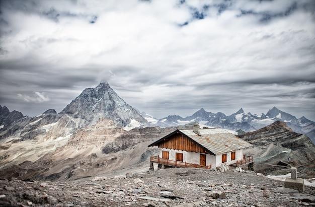 Casa de inverno com telhado de madeira no interior de uma paisagem montanhosa