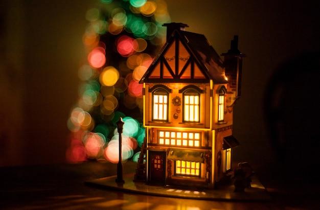 Casa de inverno feita de papelão feito com as mãos na mesa, casa brilho, decoração para o natal e árvore de natal ao fundo, luzes
