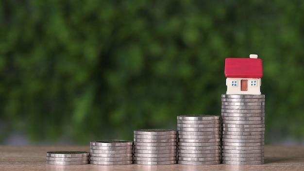 Casa de investimento de propriedade comercial e empilhamento de moedas, economizando crescimento na mesa de madeira e fundo verde para o conceito de publicidade de imóveis financeiros