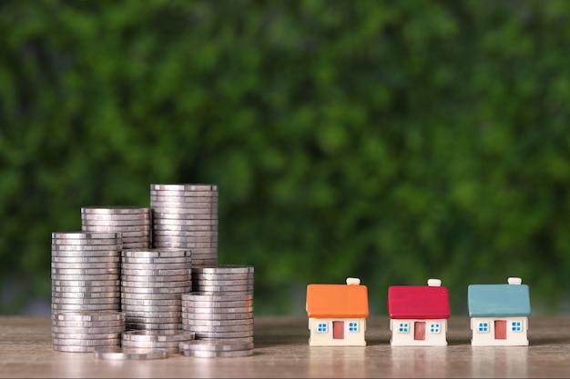 Casa de investimento de propriedade comercial e empilhamento de moedas, economizando crescimento na mesa de madeira