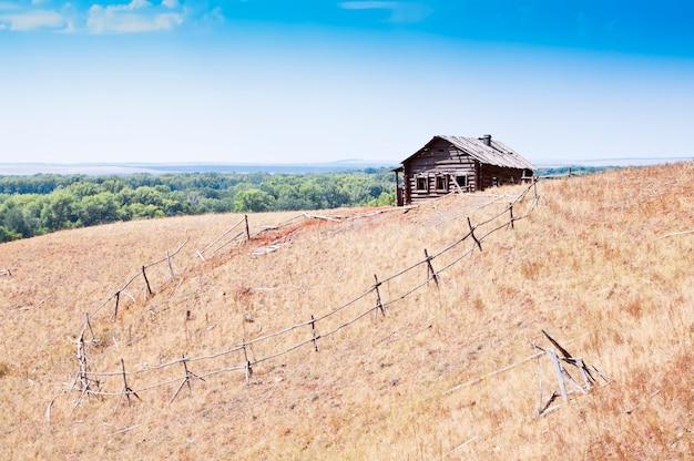 Casa de madeira abandonada em uma colina