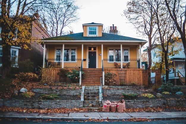Casa de madeira amarela no outono