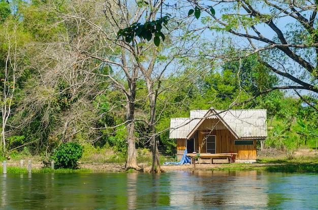 Casa de madeira ao longo do rio, tailândia