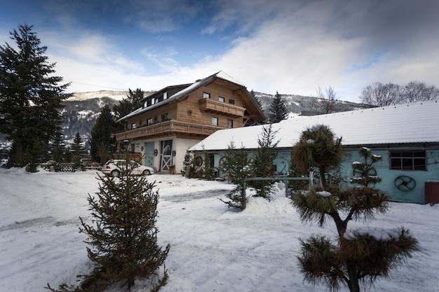 Casa de madeira austríaca tradicional em uma floresta de pinheiros em um dia de neve