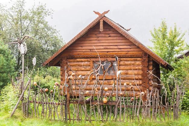 Casa de madeira autêntica com um vaso de cerâmica, persianas e suportes de janelas