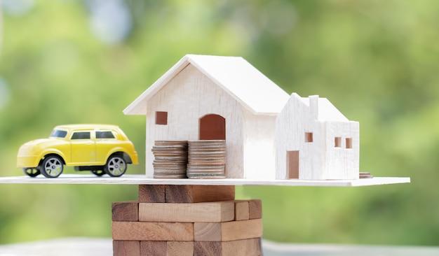 Casa de madeira, carro com pilha de dinheiro moedas na escala de blocos de madeira