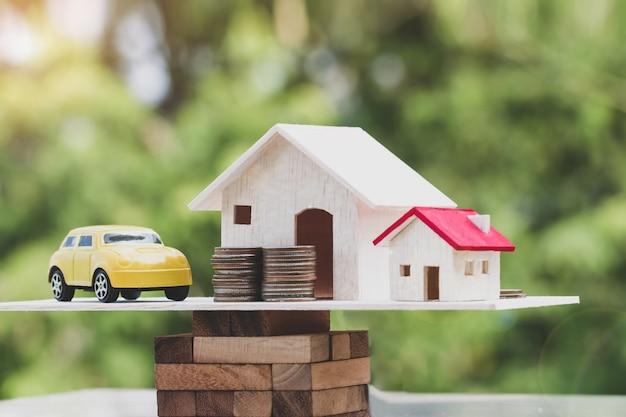 Casa de madeira, carro com pilha de dinheiro moedas no bloco de madeira