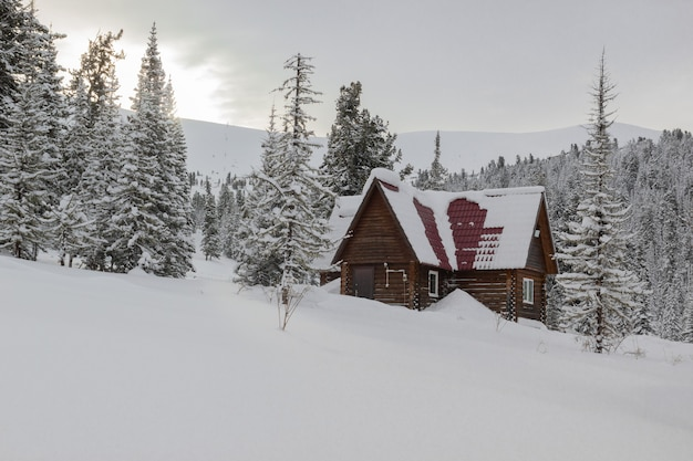 Casa de madeira cercada por montes de neve nas montanhas no inverno