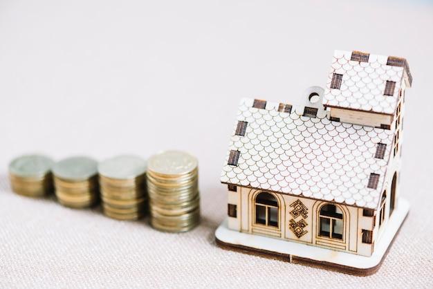 Casa de madeira close-up perto de pilhas de moedas