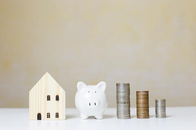 Casa de madeira com cofrinho branco e moedas de dinheiro da pilha na mesa, investimento imobiliário, economizando para o futuro, investimento de dinheiro para comprar casa. conceito de negócio de investimento.