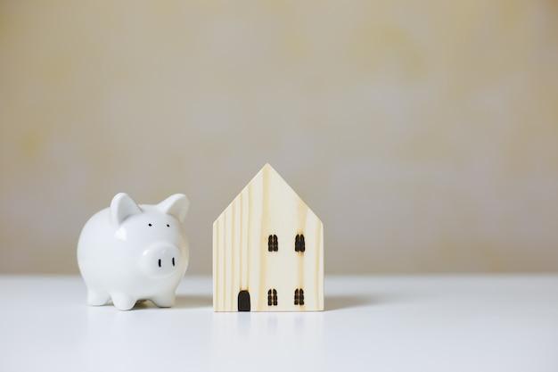 Casa de madeira com cofrinho branco na mesa, investimento imobiliário, economizando para o futuro, investimento de dinheiro para comprar casa. conceito de negócio de investimento.