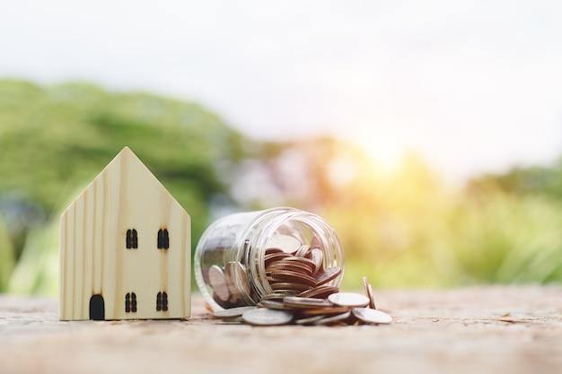 Casa de madeira com moedas derramadas do vidro do frasco na mesa desfocar o fundo da natureza, investimento imobiliário, poupar dinheiro para o futuro, dinheiro investimento para comprar casa. conceito de negócio de investimento.
