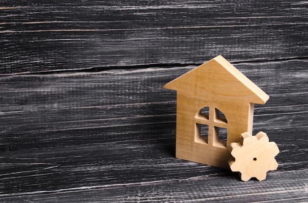 Casa de madeira com uma engrenagem em um fundo de madeira escura.
