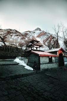 Casa de madeira contra colinas nevadas no inverno