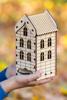 Casa de madeira de brinquedo em mãos humanas no fundo desfocado_