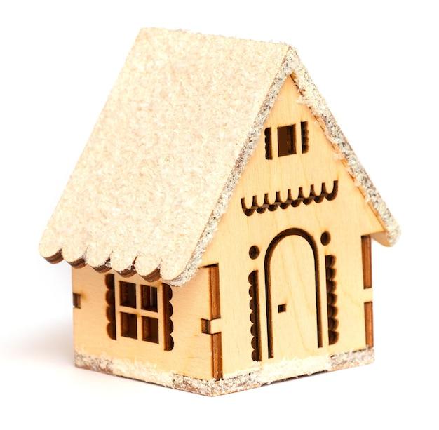 Casa de madeira de brinquedo em um fundo branco isolado como uma decoração de natal e ano novo