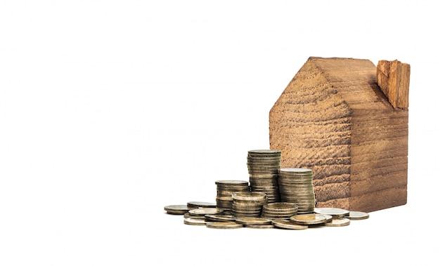 Casa de madeira diminuta com a moeda no fundo branco, conceito da propriedade