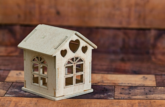 Casa de madeira do brinquedo pequeno no fundo de madeira.