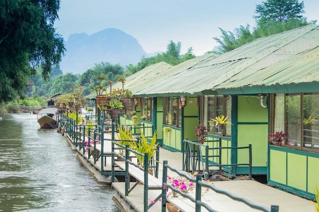 Casa de madeira do resort flutuante e nevoeiro da montanha no rio