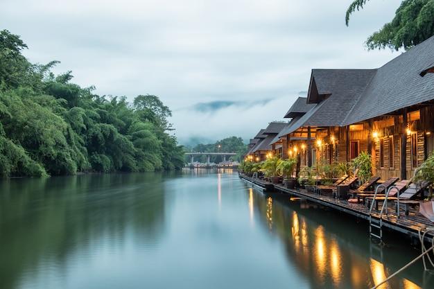 Casa de madeira do resort flutuante e nevoeiro de montanha no rio kwai
