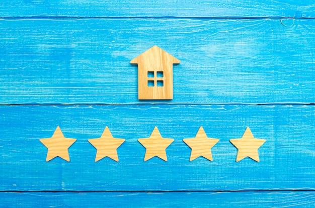 Casa de madeira e cinco estrelas em um fundo cinza. classificação de casas e propriedade privada.