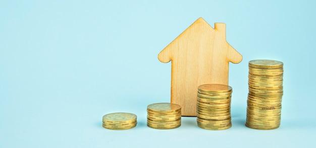 Casa de madeira e pilhas de moedas em fundo azul claro
