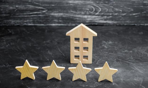 Casa de madeira e quatro estrelas em um fundo cinza. classificação de casas e propriedade privada.