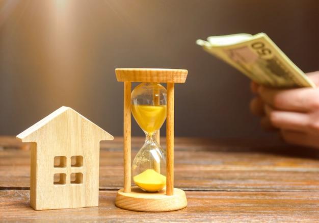 Casa de madeira e relógio. homem negócios, contagem, dinheiro