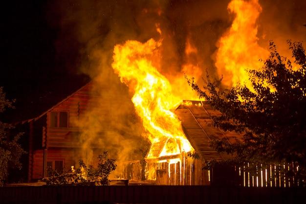 Casa de madeira em chamas à noite. chamas alaranjadas brilhantes e fumaça densa sob o telhado de azulejos no céu escuro, silhuetas de árvores e fundo de chalé residencial vizinho. conceito de desastre e perigo.