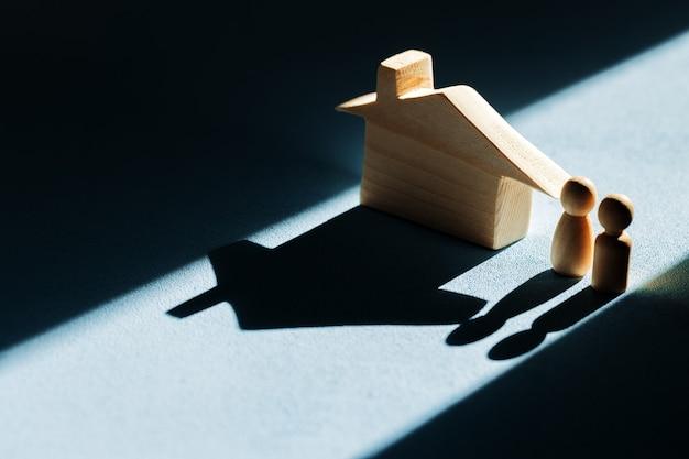 Casa de madeira em miniatura com sombras no fundo azul