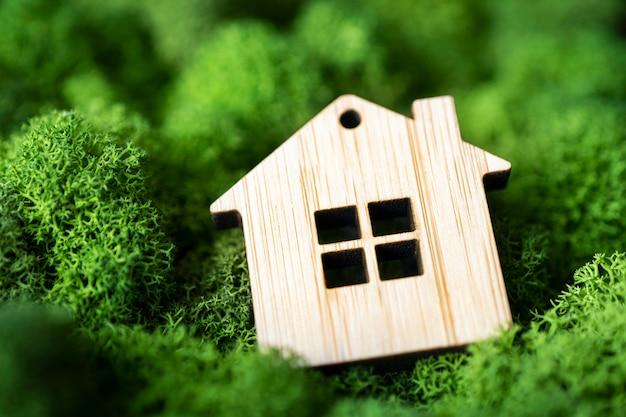 Casa de madeira em miniatura em musgo verde. o conceito de venda, seguro ou aluguel de bens imóveis. pequena cabana sobre um fundo verde de musgo natural. morar em um lugar ecologicamente correto.