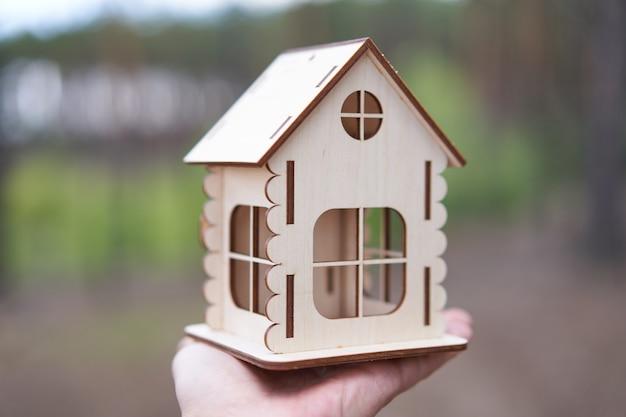 Casa de madeira em miniatura na natureza ao ar livre mão masculino